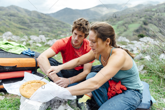 Young couple sharing a home made pie on the forest, Asturias, Spain