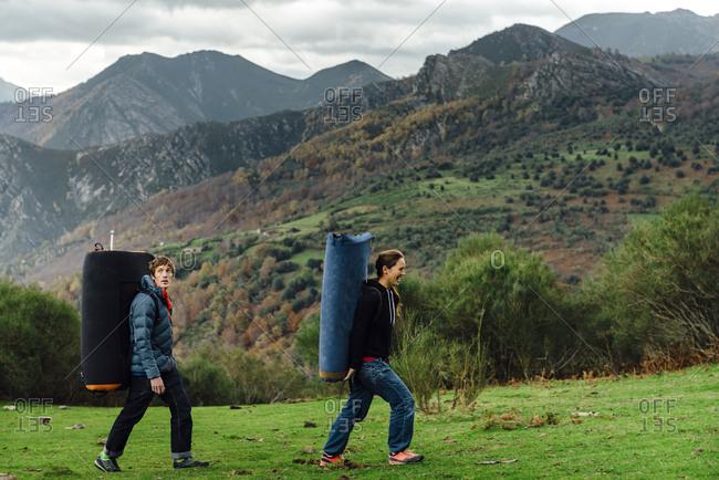 Couple of climbers carrying a crash pad after boulder climbing, Asturias, Spain