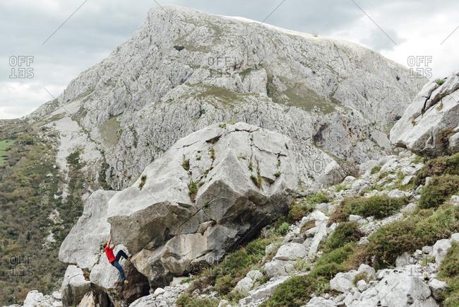 Woman rock climber  climbing overhanging boulder in scenic landscape, Asturias, Spain