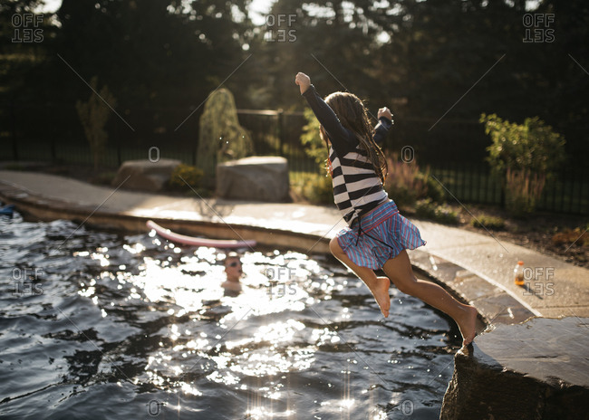 Girl leaping into a pool