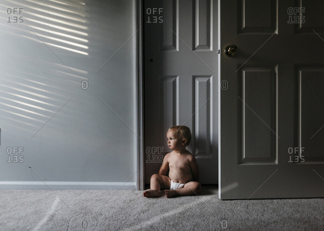 Toddler sitting on carpet in sunlight