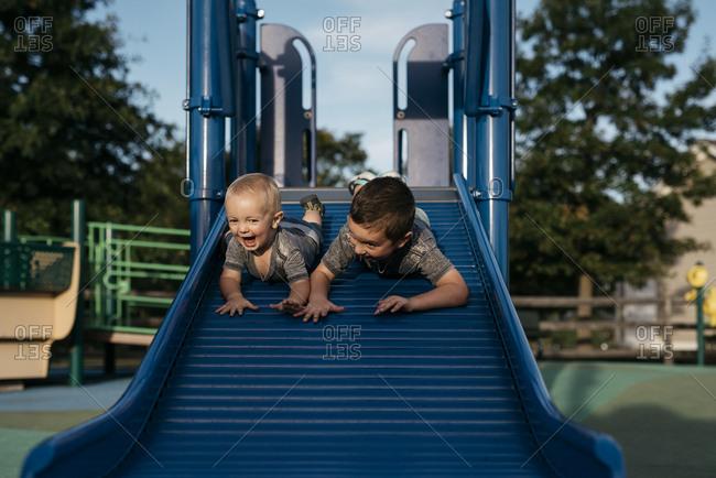 Boys going down slide together