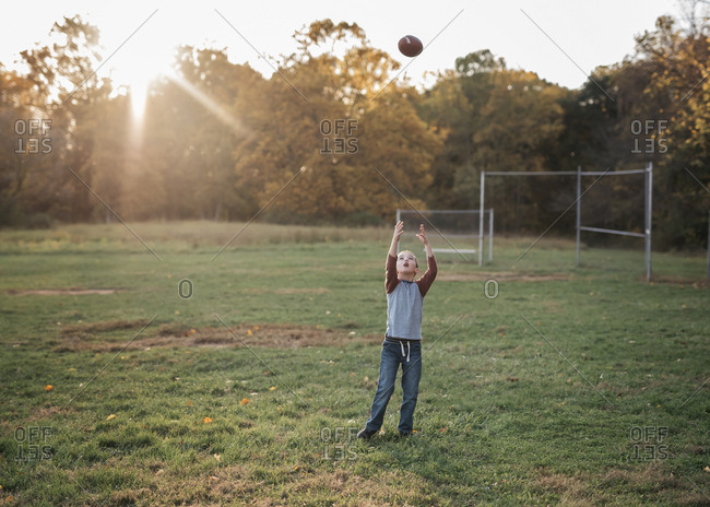 Boy catching football in rural field