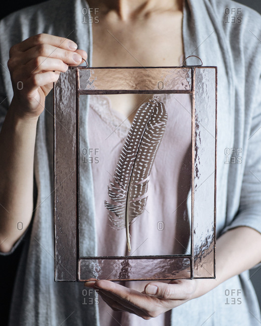 Woman holding feather in glass