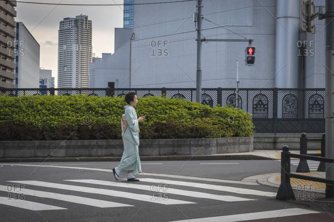 6/14/17: Japanese woman in a kimono walking at a zebra crossing in the Tsukiji area, Tokyo, Japan