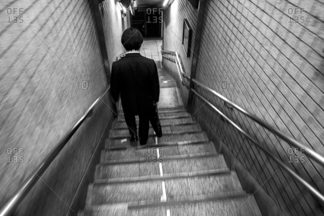 Japanese businessman in a suit walking down staircase at Higashi-Ginza station, Tokyo, Japan