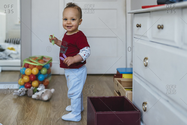 Smiling toddler boy playing with toys in a kitchen