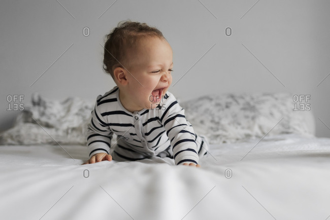 Baby boy playing on bed
