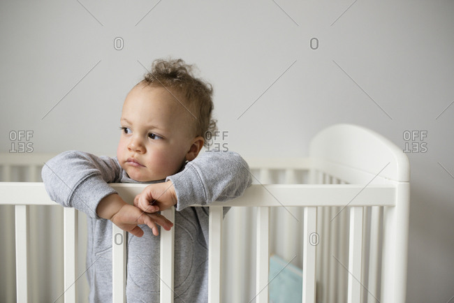 Baby standing in crib looking away