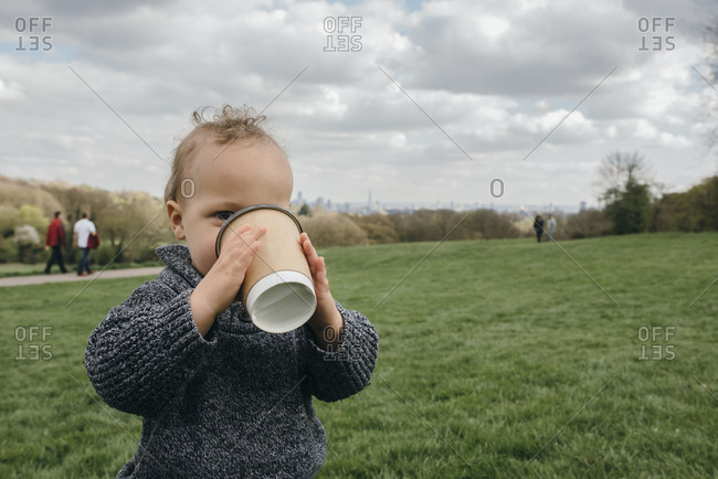 Little boy pretending to drink from a cup of coffee