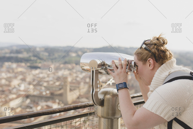 Florence, Italy - February 20th, 2016: Women looking through binoculars at the city of Florence