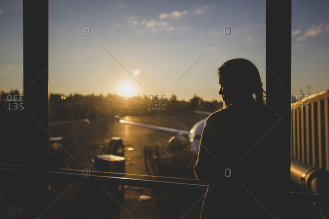 Girl patiently waiting for her flight at sunrise at the airport