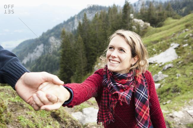 Man helping woman climb up a mountain