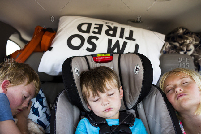 Three young siblings asleep in back seat on road trip
