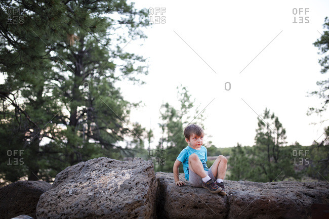 Young boy climbing on rock in woods