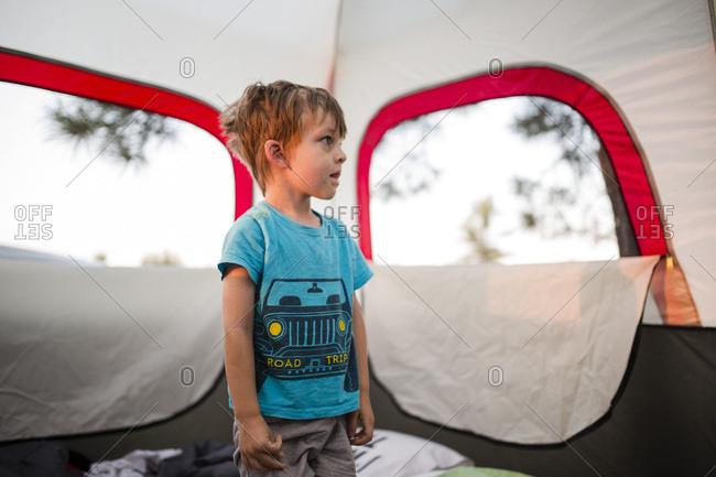 Little boy inside tent at dusk