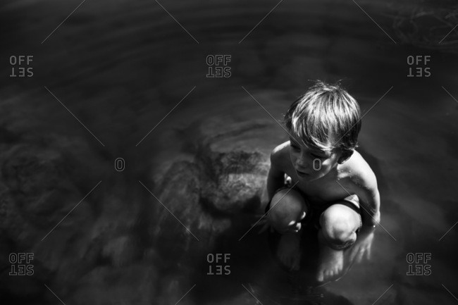 Young boy crouched on rocks in river