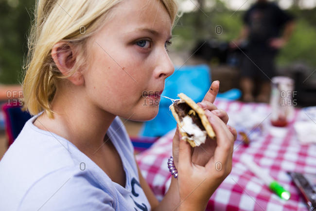 Girl eating a s'more at campsite