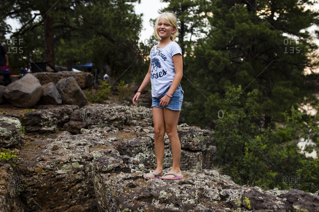 Young girl climbing on rocks at camp site
