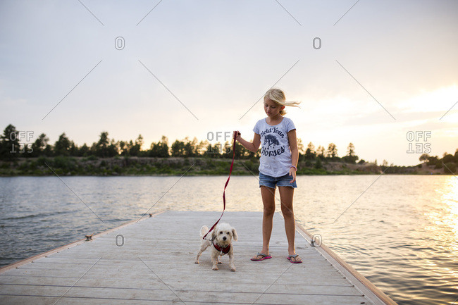 Girl with pet dog on dock