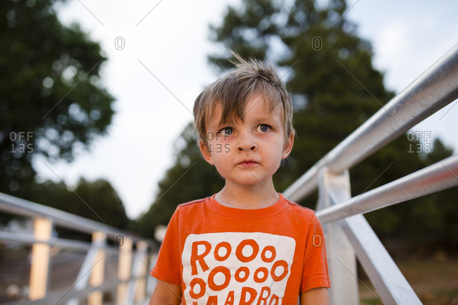 Portrait of a young boy standing on a walkway