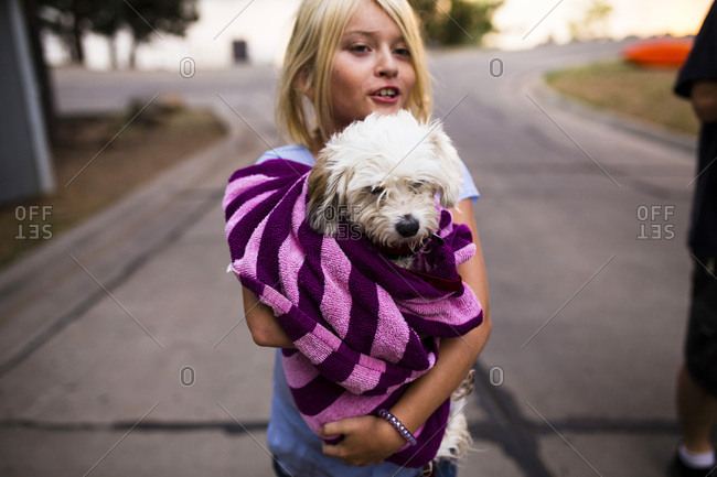 Girl carries her dog wrapped in a towel