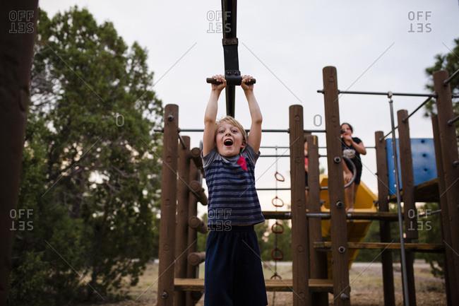 Boy playing on playground zip line