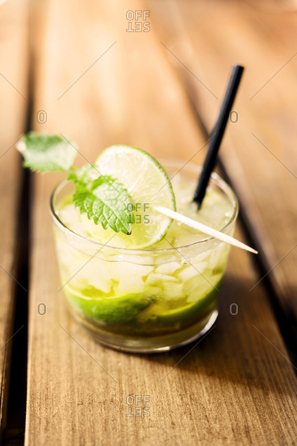 Green drink with lime on wooden table