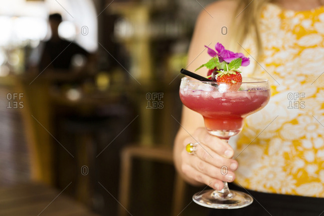 Mid section of woman holding colorful cocktail