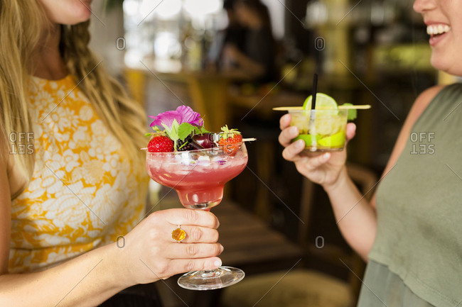 Mid section of two women holding colorful cocktails