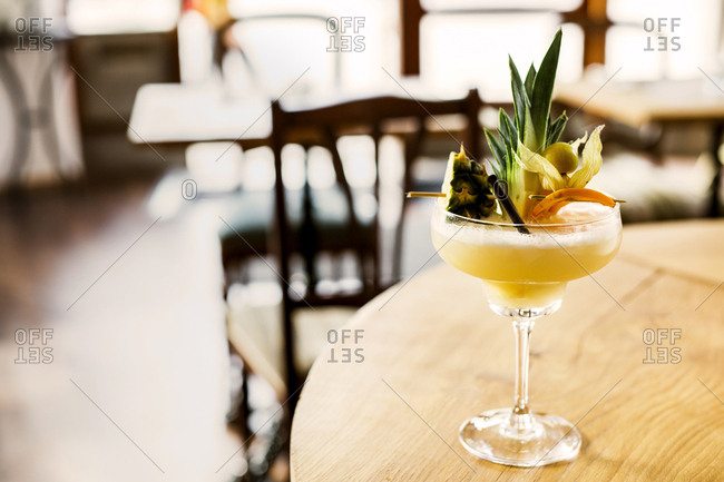 Yellow cocktail with fresh fruits on wooden table
