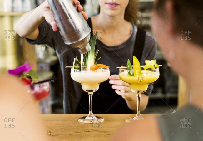 Mid section of bartender preparing colorful cocktails