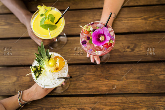 Overhead view of hands holding colorful cocktails