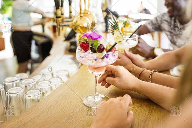 Young people with colorful cocktails in restaurant
