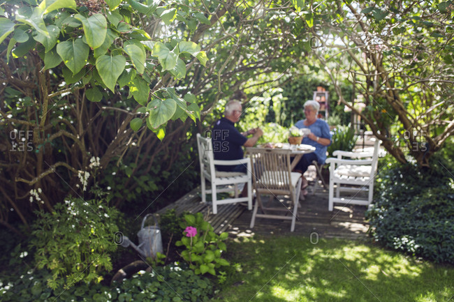 Senior woman and man sitting on patio in garden