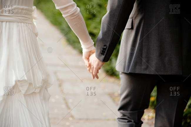 Bride and groom holding hands in a park