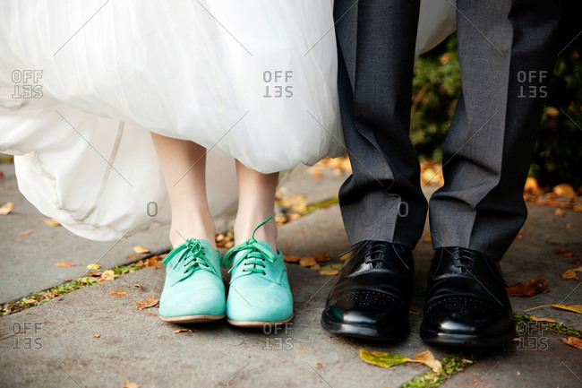Feet of a bride and groom in blue and black loafers
