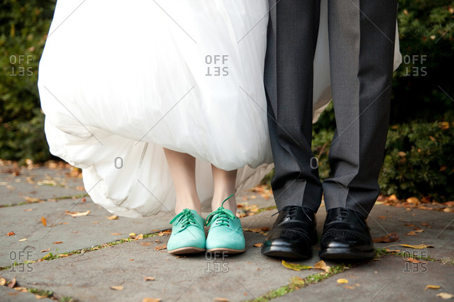 Feet of a bride and groom in blue and black loafers on a sidewalk