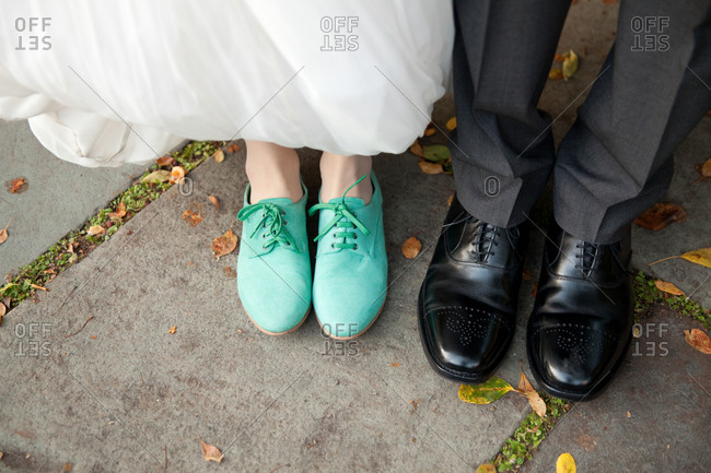 Shoes of a bride and groom standing on a sidewalk in a park