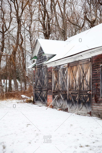 Weather-worn barn with many doors in the snow