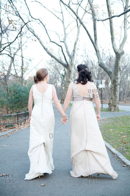 Two brides holding hands walking on a path in Central Park
