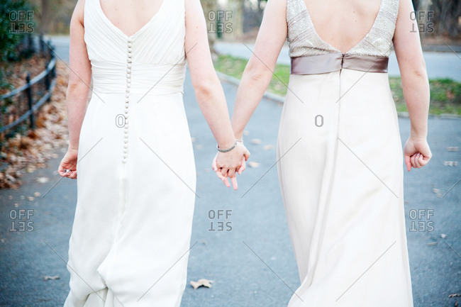 Newlywed brides holding hands on a path in Central Park