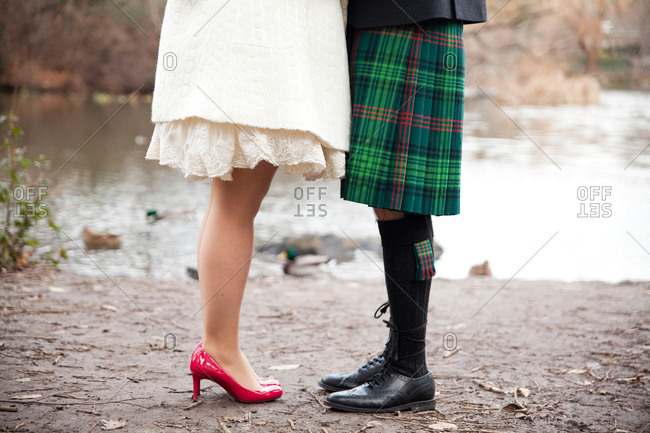 Newlyweds in red heels and a green kilt standing on the edge of a pond