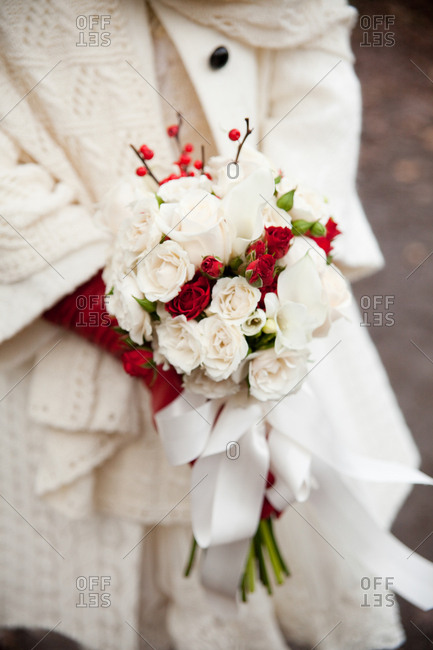 Bride wrapped in a white sweater holding a bouquet of red and white roses