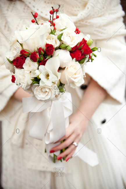 Bride standing outdoors holding a bouquet of red and white roses