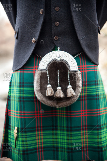 Groom in a green kilt standing outdoors