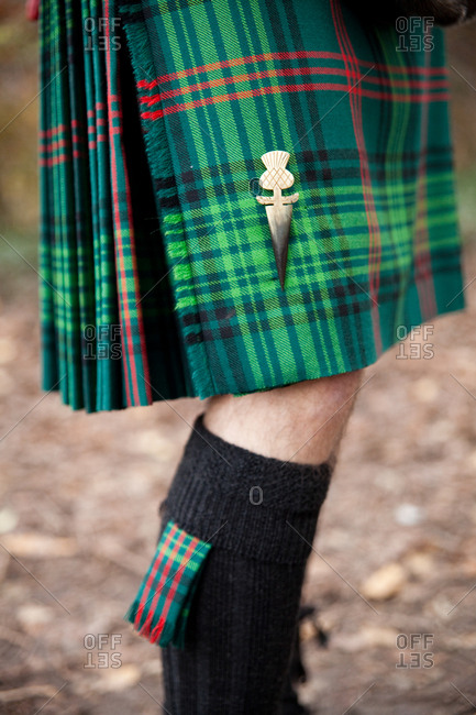 Groom in a green kilt and tall wool socks standing outdoors