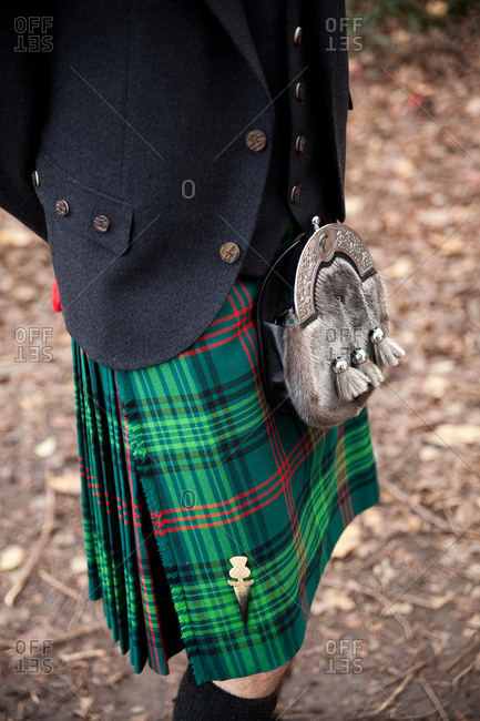 Groom in a green kilt and sporran standing in a park