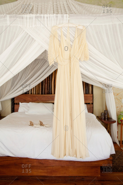 Cream-colored wedding gown hanging from a canopy over a bed