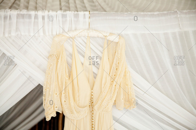 Cream-colored wedding gown with beads hanging from a bed canopy